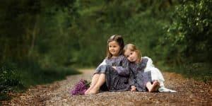 Geschwister auf Waldweg sitzend