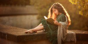 Kinderfotografie - Kind liest ein Buch im Sonnenuntergang