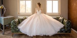 Braut mit Prinzessinnenkleid sitzt auf Couch