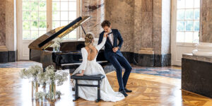 bilderschlag Braut sitzt am Klavier und Bräutigam küsst sie